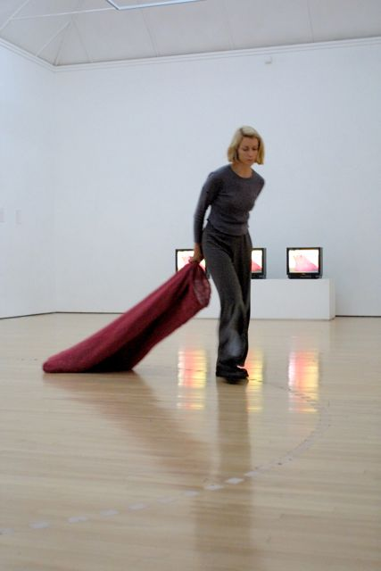 the artist dragging a red sack around a gallery with monitors behind