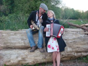photo of nigel )sax) and delph (acorrdion on a log outside