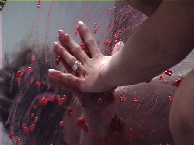 a hand rubbing raspberries onto a mirror