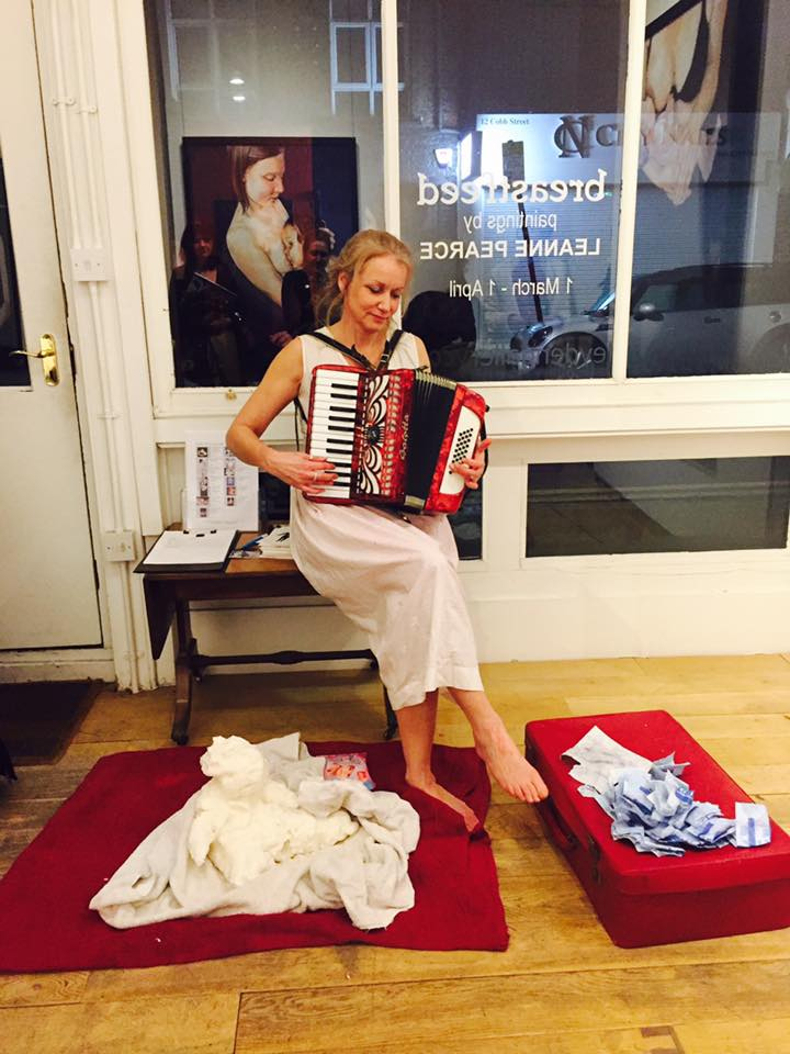 playing an accordion as part of a performance called double burden