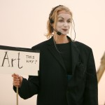 image of artist with clown white face holding a sign that says art this way?