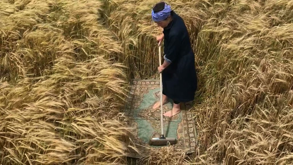 film still of woman sweeping arug in the middle of a field